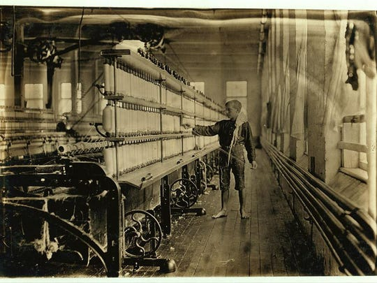 Young boy at work in a Burlington cotton mill.