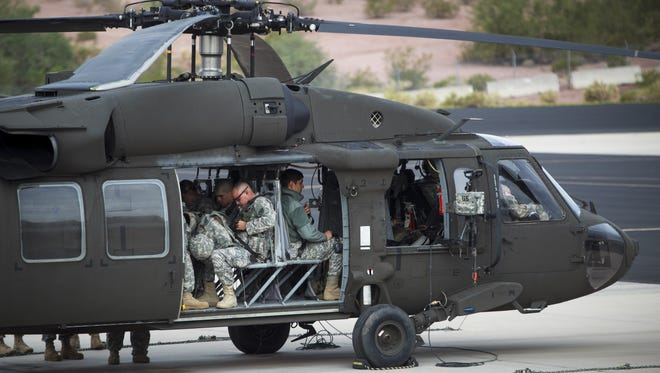 About a dozen members of the Arizona Army National Guard prepare to leave on a Blackhawk  helicopter at the Papago Park Military Reservation in Phoenix  on Friday, Oct. 12, 2012, for troop training