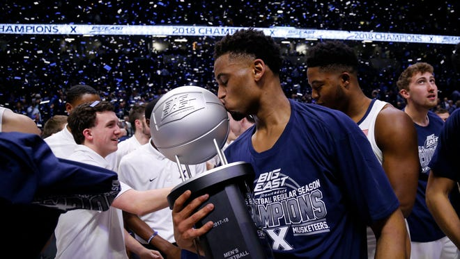 Xavier Musketeers guard Trevon Bluiett (5) kisses the Big East regular season championship trophy after the NCAA Big East game between the Xavier Musketeers and the Providence Friars at the Cintas Center in Cincinnati on Wednesday, Feb. 28, 2018. The Musketeer won its first-ever Big East regular season title with an 84-74 win over Providence.