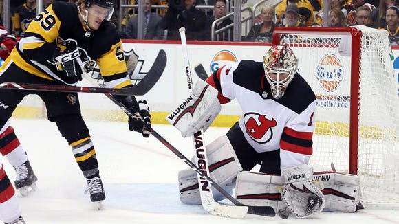 New Jersey Devils goaltender Keith Kinkaid (1) makes a save against Pittsburgh Penguins center Jake Guentzel (59) during the second period at PPG PAINTS Arena on Friday, March 24, 2018.