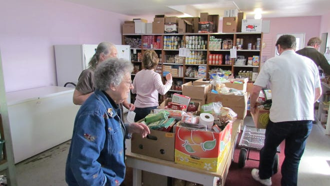 Stayton Community Food Bank Manager Edna Rickman, left, oversees volunteers of all ages assembling food boxes on Friday, March 7, 2014.