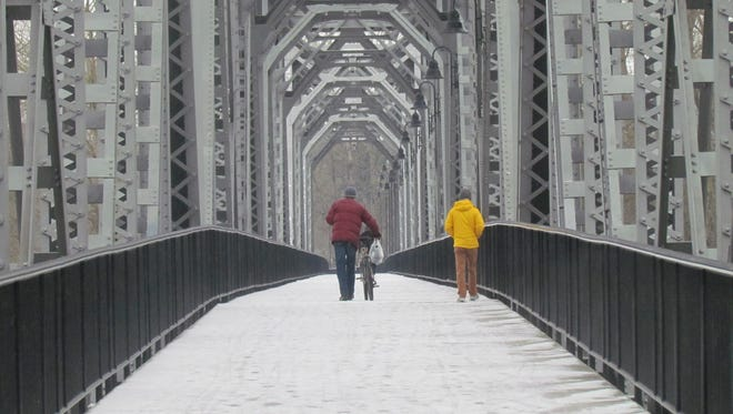 Pedestrians negotiate their way over a snow-frosted Union Street Bridge Sunday.