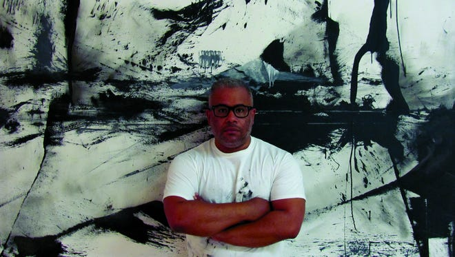 """Marcus Jansen poses with his painting """"Phase 1,"""" which he created on camera for the new documentary """"Examine & Report."""""""