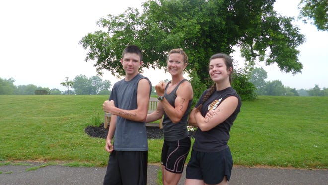 Austin Hill, left, and his sister Macy Hill, right, pose with their mother, Megan Bookless, center, at the 2014 Indian Mud Run. Bookless has topped the women's division of the 5K fundraiser for the past three years.