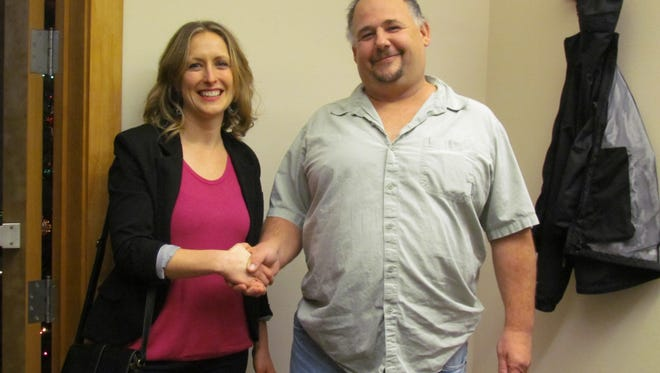 Mill City City Council candidates Hannah Baker, left, and Scott J. Baughman shake hands following a die roll for the seat. Each candidate received a tying 395 votes in the Nov. election. Baughman's roll of five topped Baker's two.