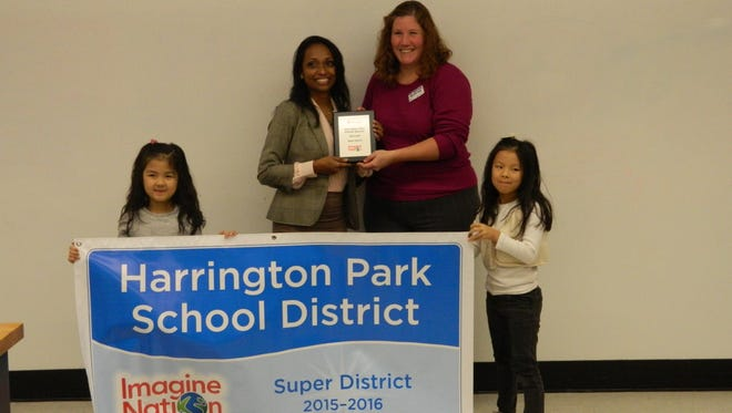 Sheba Koshy receives honor for Harrington Park School as Super District from Imagine Learning. Heather Hay is representing Imagine Learning in the picture. Twin first-grade girls, Isabella Oh on left and Alyssa Oh stand on the right