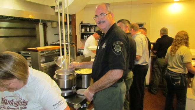 A legion of volunteers, including Stayton Police and Marion County Sheriff's Office personnel, pitch in to feed the community during the annual Stayton Community Dinner hosted by Covered Bridge Cafe.