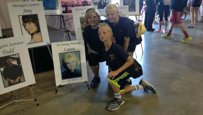 Dr. Karla Loken poses with her twins next to a photo of her late sister, Laura Loken. Laura died in 1988 at age 16 of meningitis B. Karla and her sons were attending a memorial race to raise money for meningitis vaccines and to honor victims of the disease.
