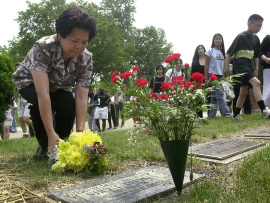 Amy Lee, aunt of Vincent Chin, places flowers at the
