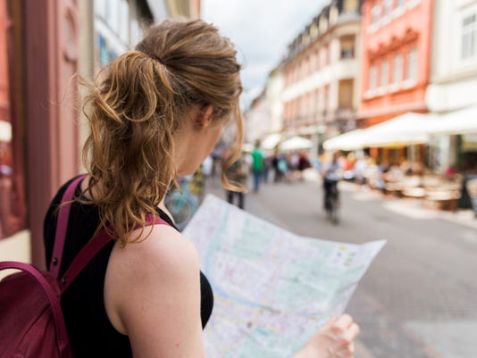 Tourist holding a street map in hands and looking for the way background