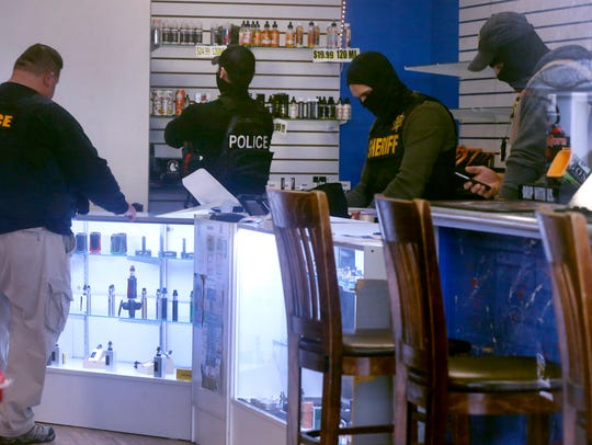 Law enforcement agents collect evidence from Vapesboro, one of 23 stores closed for selling products believed to contain a marijuana derivative.