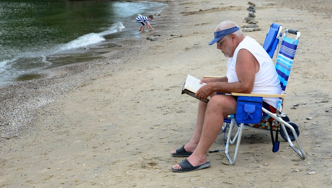 Steve Andres of Salem reads a book at City Beach. Now retired for the past six years, he said he reads eight to 10 books each summer.