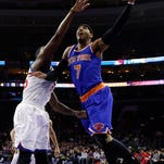 New York Knicks' Carmelo Anthony, right, goes up for a shot against 76ers' Henry Sims during the first half Wednesday in Philadelphia.