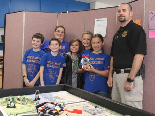 Ryne Cerra, Coach Sarah Cerra, Caleb Watts, Ayden Parra, Isabella Haas, Mica Gonzales and Coach James Watts pose together with their robot Michael.