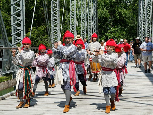 The Voyageur Ancient Fife & Drum Corps leads guests across the Gray Bridge during a ribbon cutting to dedicate the structure Saturday, July 5, 2014, as part of Delphi's Canal Days Festival in Wabash & Erie Canal Park. The 132 foot iron bridge, built in 1913. once spanned Big Walnut Creek in Putnam County.