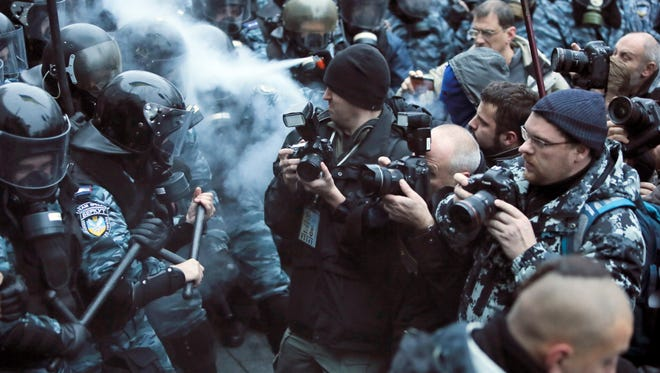 Photographers take photos during a fight between opposition protesters and riot police in front of the Ukrainian Cabinet of Ministers in Kiev, Ukraine on Sunday.