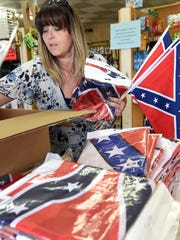 Carrie Faso of PGW Collectibles in Lakeview unpacks a shipment of Confederate flags on Monday. Sales at the store have been brisk since controversy over the flag erupted following the shooting of nine people in Charleston, S.C. PGW has a waiting list of people wanting to purchase the flag.