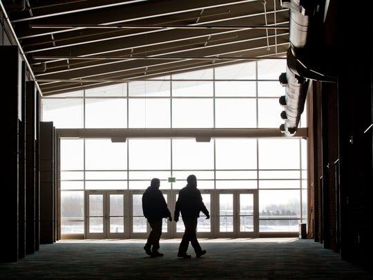Contractors look over details of completed work in the main hallway.