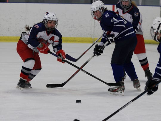 Vying for a loose puck are Loren Hitch (left) of the PCS Penguins and Regina's Eliza Kain.