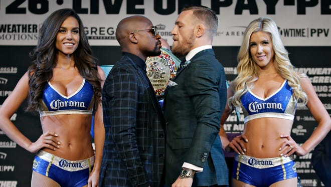 Floyd Mayweather Jr. and Conor McGregor pose for photos Aug. 23 in Las Vegas.