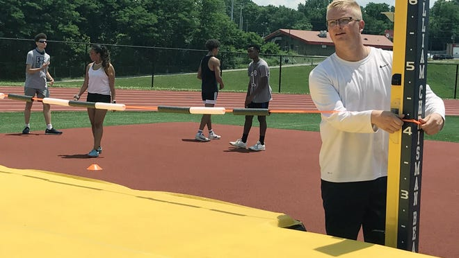 William Chrisman track and field coach Tyler Rathke, right, adjusts the height of the bar as he works with the high jumpers as the Bears prepare for the All-Independence Track and Field Meet against Truman and Van Horn July 2 at Chrisman Stadium.