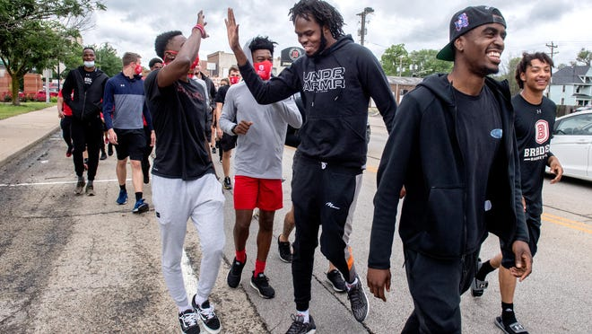 Bradley basketball players greet their teammate Koch Bar, middle, as he joins them a few blocks in during a peaceful protest and march by Bradley University athletes Tuesday, June 9, 2020 from Renaissance Coliseum to the Peoria Civic Center.