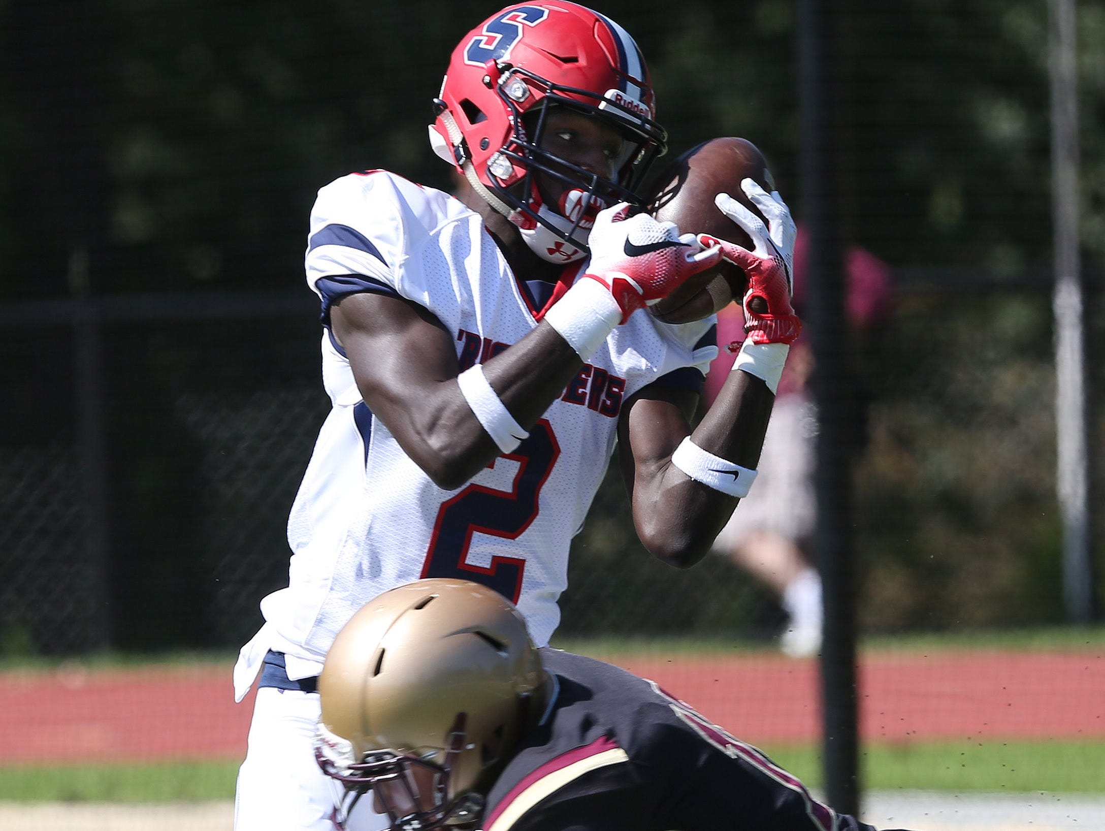 Stepinac's Atrilleon Williams (2) catches a touchdown pass while being ht by Iona's Michael Degasparis (10) for his first touchdown of the game, during football action at Iona Prep in New Rochelle Sept. 17, 2016. Stepinac won the game 42-34.