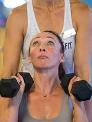 Amy Van Dyken-Rouen does a set of dumbbell lifts in 2014.
