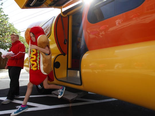 Dressed as a hot dog, 9-year-old Sophia Ross walks out of the Wienermobile after taking a look at the inside of the hot dog on wheels on Thursday, August 21, 2014.