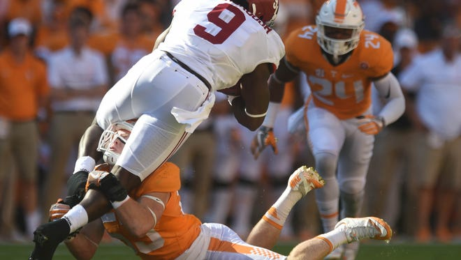 Alabama running back Bo Scarbrough (9) is tripped up by Tennessee linebacker Colton Jumper (53) during the first half at Neyland Stadium on Saturday, Oct. 15, 2016.
