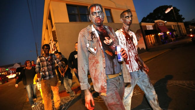 Zombies Danny Traub, middle, and Robert Nohl, both of Indianapolis, make their way down Broad Ripple Avenue during the seventh-annual Broad Ripple Zombie Walk to benefit Gleaner's Food Bank on Oct. 25, 2014.