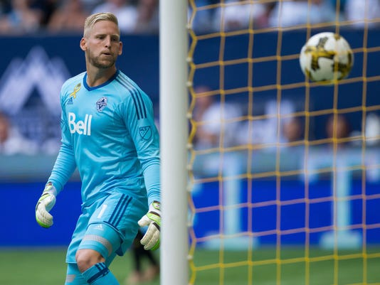 Vancouver Whitecaps' goalkeeper David Ousted watches as the ball enters the net off the foot of Columbus Crew's Ola Kamara for a goal during the first half of an MLS soccer game in Vancouver, British Columbia, Saturday, Sept. 16, 2017. (Darryl Dyck/The Canadian Press via AP)
