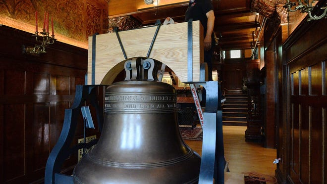 Hagen History Center employee Rob Bronson checks the lighting on the replica Justice Bell inside the Watson-Curtze Mansion on Thursday. The replica, which is based on a replica of the Liberty Bell, will be displayed July 8 at an invitation-only event co-organized with the Erie County Chapter of the League of Women Voters.