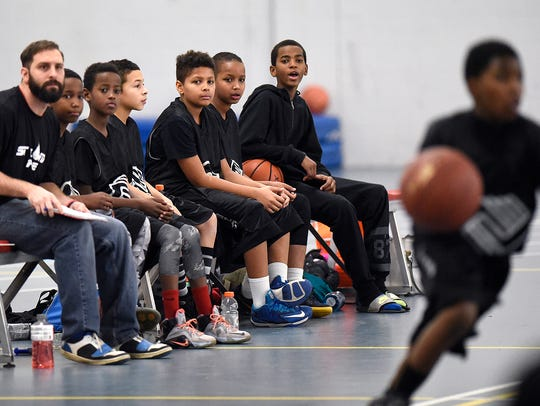 Boys & Girls Club players watch from the bench during