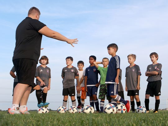 Marcello Cioffi, a coach for the GPS Delaware Revolution, instructs youth soccer players before a passing drill at the Middletown sports complex on Level Roads.
