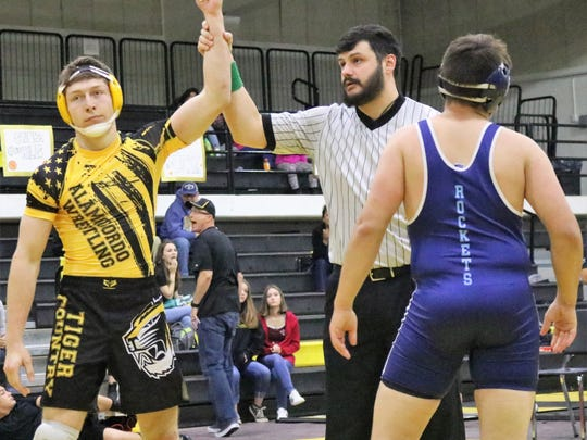 Alamogordo's Devin Brown, left, celebrates a victory over a Goddard wrestler.
