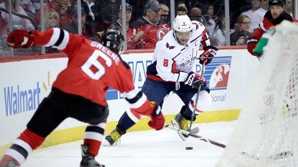 Washington Capitals left wing Alex Ovechkin (8), of Russia, skates with the puck as New Jersey Devils defenseman Andy Greene (6) tries to defend during the first period of an NHL hockey game Thursday, Jan. 18, 2018, in Newark, N.J. (AP Photo/Julio Cortez)
