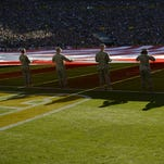 Soldiers take part in holding a large American flag during the playing of the national anthem before a 2015 game at Lambeau FIeld.