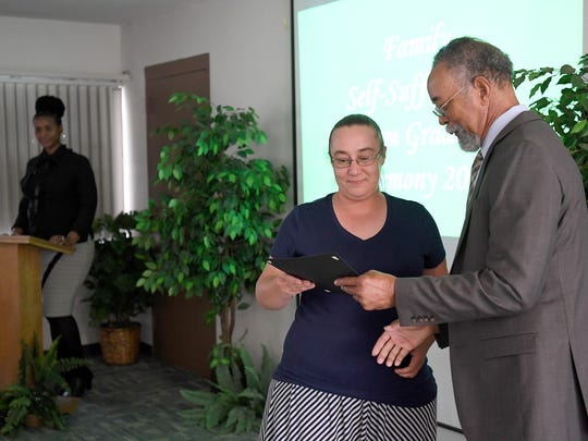 Sabrina Hatfield receives a certificate from Asheville Housing Authority CEO Gene Bell during a Family Self-Sufficiency Program graduation ceremony on Tuesday, May 30, 2017. The five-to-seven-year program is designed to improve education and job skills to cut back on welfare assistance with an ultimate goal of homeownership.