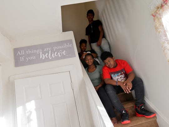 Hattie Hunter's great-grandkids sit on the renovated stairwell in their home.