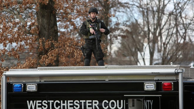 A member of the Westchester County Police Special Response Team takes up a position on a truck in Leonard Park behind the CVS in Mount Kisco Dec. 2, 2016. A report of two men with assault rifles proved to be unfounded.