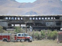 Amtrak passenger cars sit still smouldering after the train was struck by a semi truck on US 95.