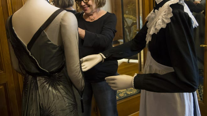 "Nancy Lawson, a costume specialist with the ""Dressing Downton: Changing Fashion for Changing Times"" collection, places the pieces on mannequins at the Paine Art Center."