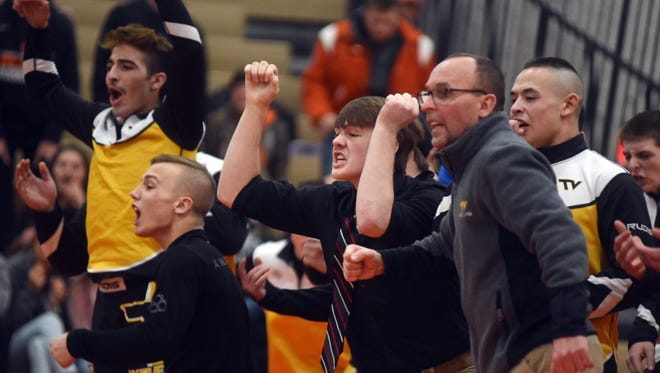 The Tri-Valley wrestling team prepares to celebrate prior to A.J. Collins records a pin at 195 pounds that clinched a 41-33 win against New Lexington on Thursday.