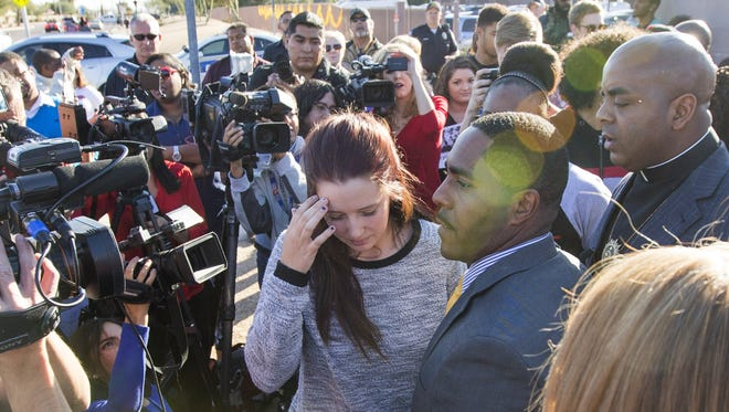 Rachel Steigerwald, one of six Desert Vista High School students who spelled the N-word using shirts in a photo that's gone viral, walks away after apologizing during a press conference at the school on Monday.