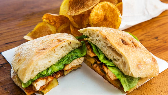 Crispy chicken sandwich with a side of potato chips from Worth Takeaway restaurant in Mesa.