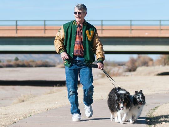 Randy Burk of Las Cruces walks his dogs Sombra, 8,