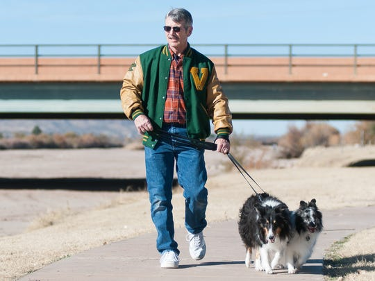Randy Burk of Las Cruces walks his dogs Sombra, 8, left, and Xander, 6, along the Rio Grande Trail near the Picacho Street Bridge.