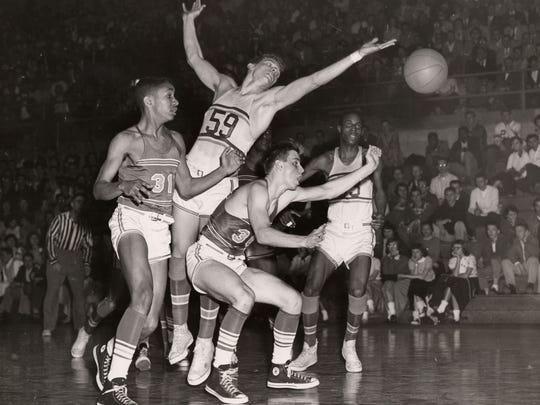 Don Brauson (31) and Roger Humm (30) play in the 1955 regional final game against Canton. Zanesville defeated Canton to advance to the state tournament.