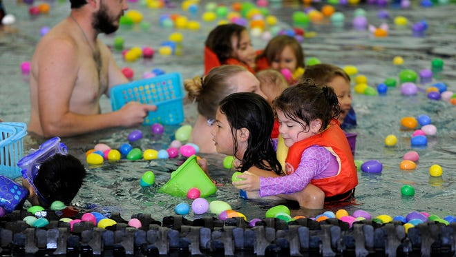 Three-year-old Lexi Tubbs (right center) grabs Easter Eggs while riding on the back of her sister, Madison (left center), 10, during the swimming pool Easter egg hunt on Saturday, April 8, 2017, at the Redbud Park YMCA.